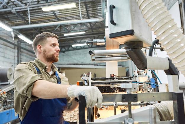 Jóvenes trabajadores de fábrica que operan la máquina