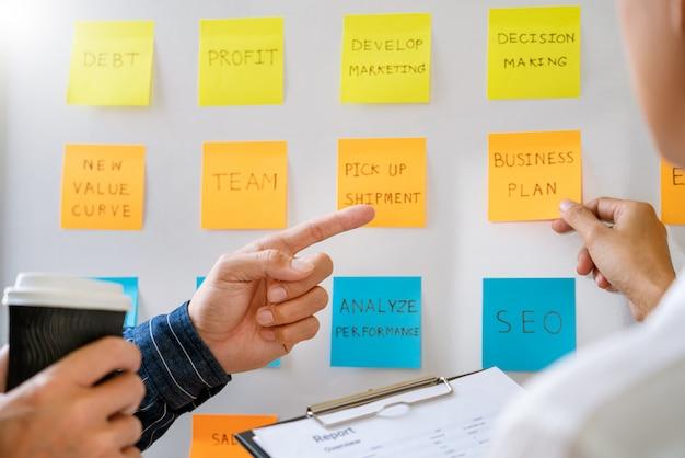Los jóvenes trabajadores de negocios que publican con notas adhesivas recordatorios creativos de lluvia de ideas a bordo del colega en un espacio moderno de trabajo conjunto
