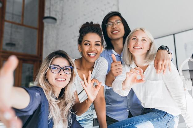 Jóvenes trabajadores de oficina internacional posando juntos y riendo durante el descanso