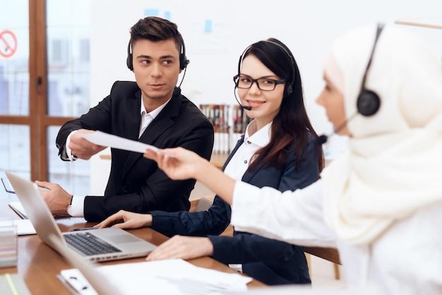 Los jóvenes trabajan con colegas en un call center.