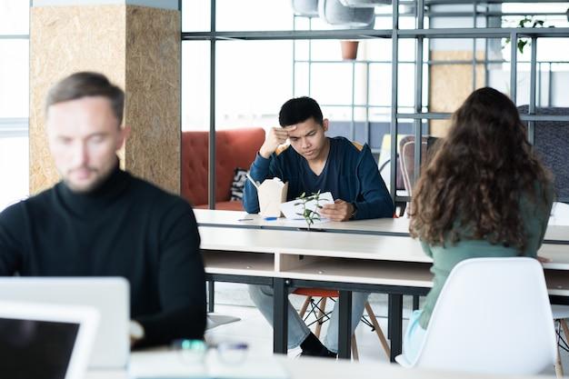 Jóvenes trabajando y comiendo en la oficina de espacios abiertos