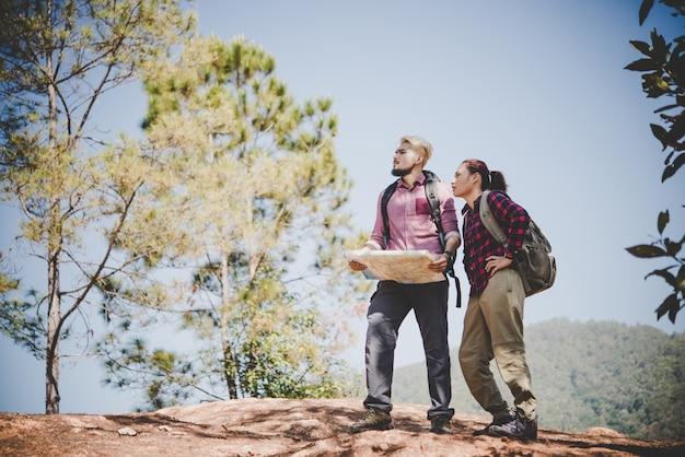 Jóvenes turista pareja viajando de vacaciones en la montaña mirando el mapa en busca de atracciones. concepto de viaje.