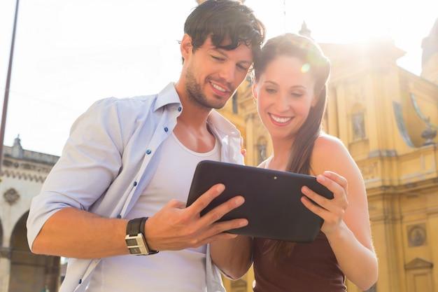 Jóvenes turistas en la ciudad con tablet pc