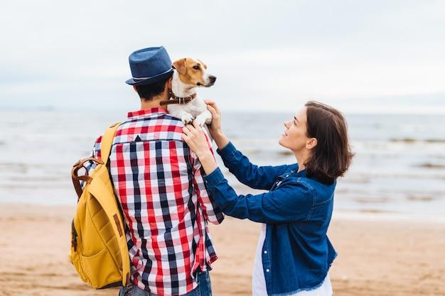 Jóvenes turistas masculinos y femeninos caminan cerca del mar, llevan a su mascota favorita, disfrutan del clima