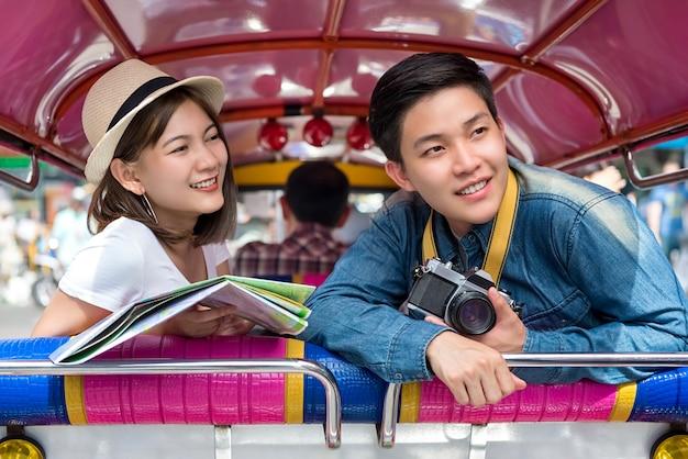 Jóvenes turistas de pareja asiática que viajan en taxis locales coloridos tuk tuk en bangkok, tailandia