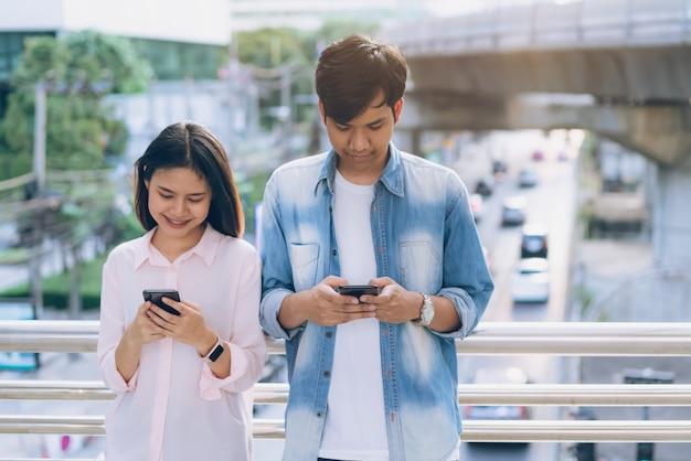 Los jóvenes usan un teléfono inteligente y sonríen mientras están sentados en el tiempo libre. concepto de tecnología
