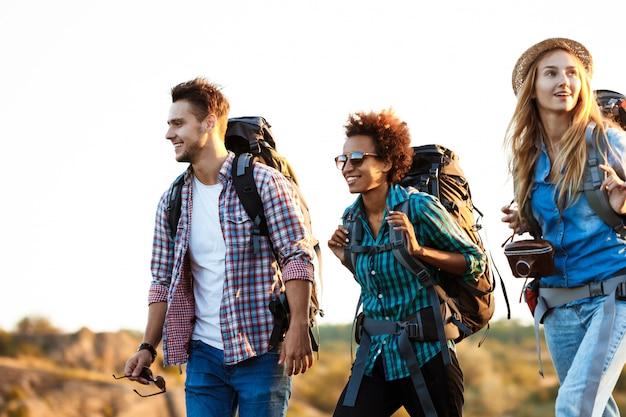 Jóvenes viajeros alegres con mochilas sonriendo, caminando en el cañón