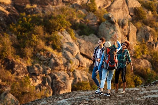Jóvenes viajeros con mochilas sonriendo, dando cinco, caminando en el cañón