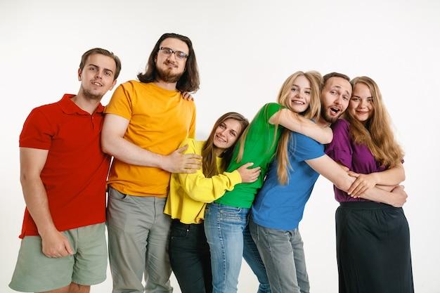 Los jóvenes se vistieron con los colores de la bandera lgbt aislados en la pared blanca concepto de orgullo lgbt