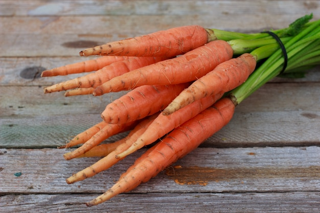 Jóvenes zanahorias frescas y hierbas verdes sobre fondo de madera vieja. alimentos orgánicos