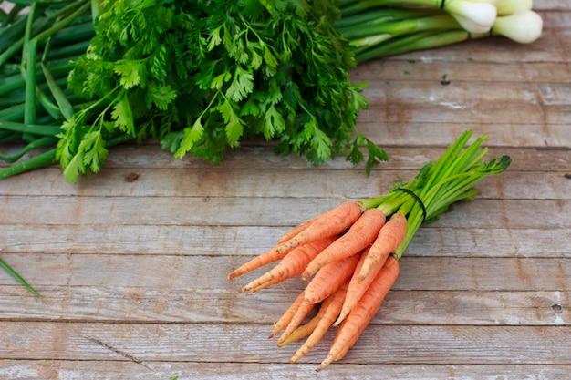 Jóvenes zanahorias frescas y hierbas verdes sobre fondo de madera vieja