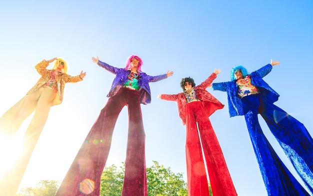 Jóvenes en zancos posando contra el cielo azul.