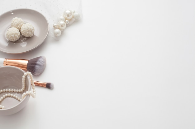 Joyas para la novia, dulces y taza de café, sobre un fondo blanco. bodas conceptuales, preparación y mañana de la novia.