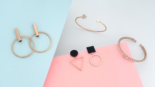 Joyas de oro modernas sobre fondo azul y rosa