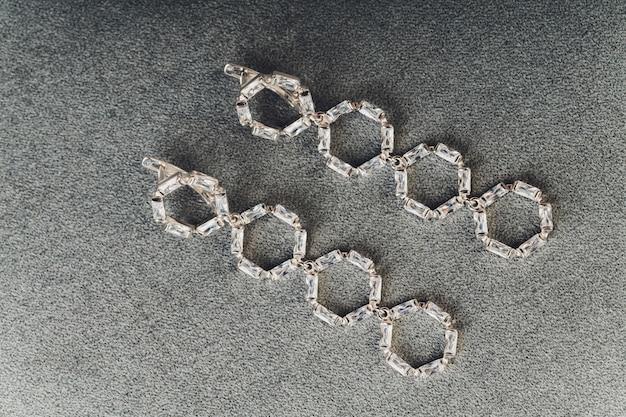 Joyas de plata y piedra blanca. pulseras de ágata, anillos de plata y aretes en una superficie clara, vista superior, plano, copia espacio. joyas de mujer sobre una superficie gris con espacio libre para texto.