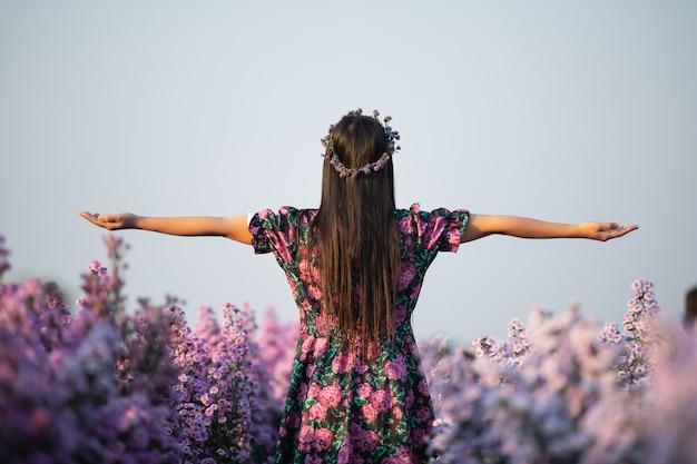 Joyfull mujer en vestido morado entre flor de margarita púrpura
