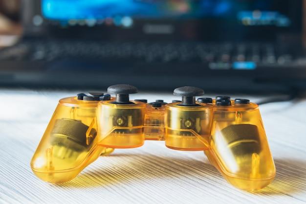 Joystick amarillo transparente y una computadora portátil con un videojuego en una mesa