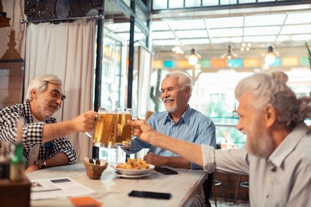 Jubilados y cerveza. jubilados sentados a la mesa en el restaurante y bebiendo cerveza por la noche