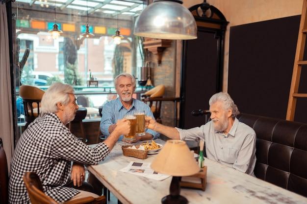 Jubilados relajantes. tres jubilados que se sienten bien mientras se relajan y beben cerveza.