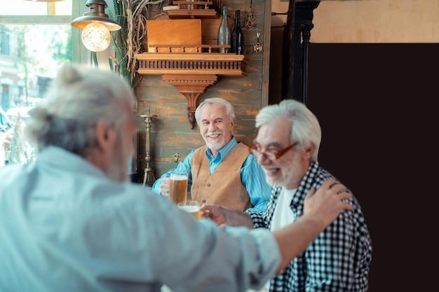 Jubilados riendo. los jubilados riendo mientras beben cerveza en el pub y hablando