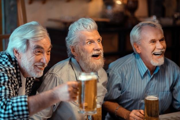 Jubilados riendo. tres jubilados riendo mientras ve el fútbol en el pub y bebiendo cerveza