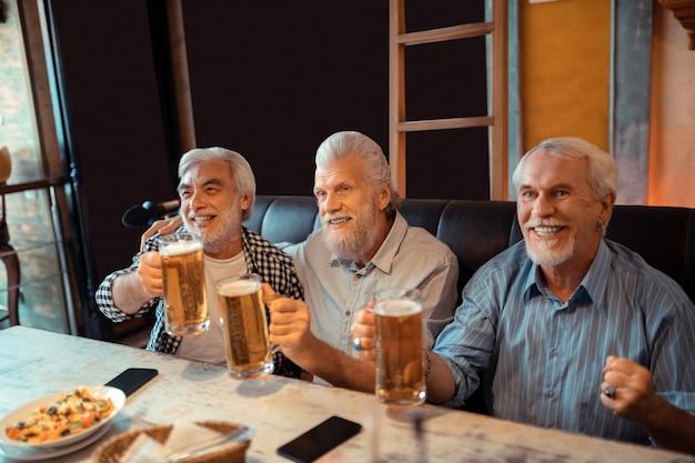 Los jubilados se sienten felices. los jubilados radiantes se sienten felices mientras beben cerveza y miran fútbol