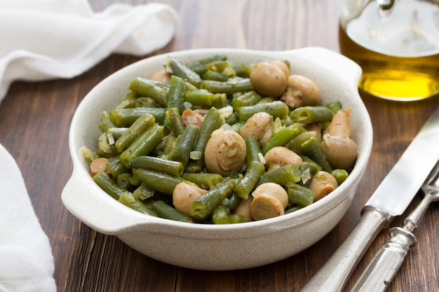 Judías verdes con champiñones en plato sobre superficie de madera