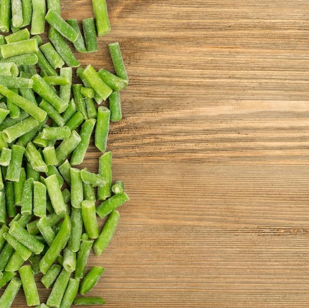 Judías verdes congeladas en vista superior de la mesa de madera