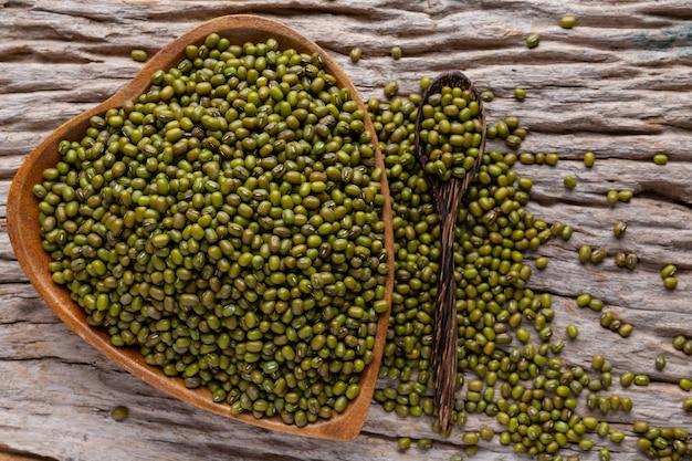 Judías verdes crudas en una taza colocada en un piso de madera.