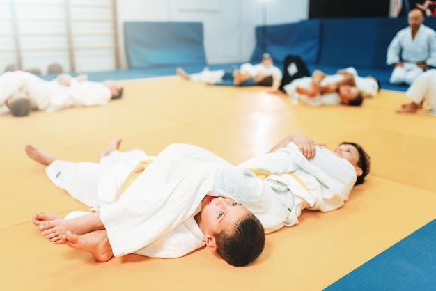 Judo infantil, entrenamiento de lucha, artes marciales, defensa personal. niños en uniforme en el gimnasio deportivo, jóvenes combatientes