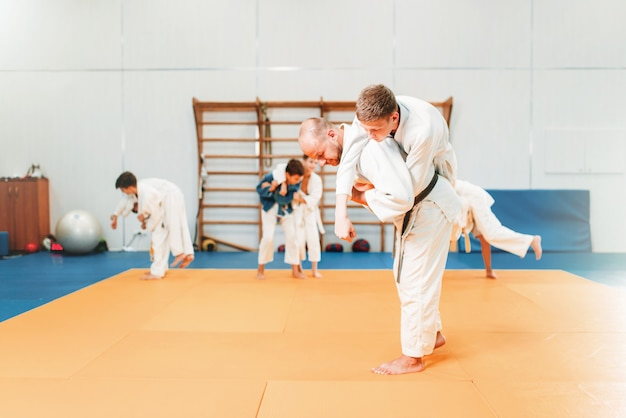 Judo infantil, jóvenes luchadores en entrenamiento en el pasillo. los niños pequeños en kimono practican artes marciales.