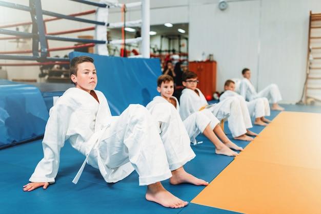 Judo para niños, niños en kimono practican artes marciales en el pasillo. niños y niñas en uniforme en entrenamiento deportivo.