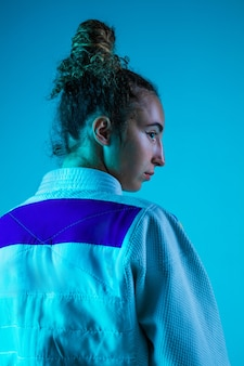 Judoista profesional femenino en kimono de judo blanco practicando y entrenando aislado sobre fondo azul neón studio.