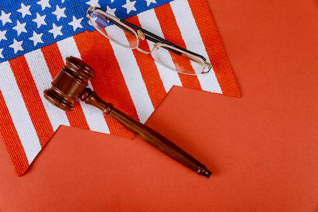 Jueces de madera mazo de gafas de lectura y bandera de ee. uu. en la mesa del juez