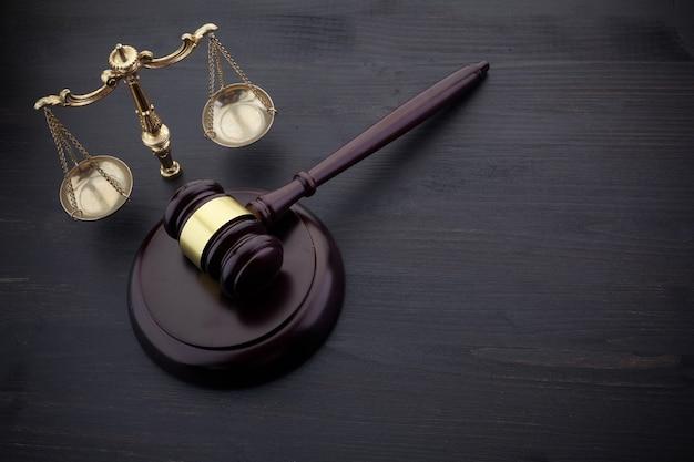 Jueces martillo y escala de justicia sobre la mesa negra