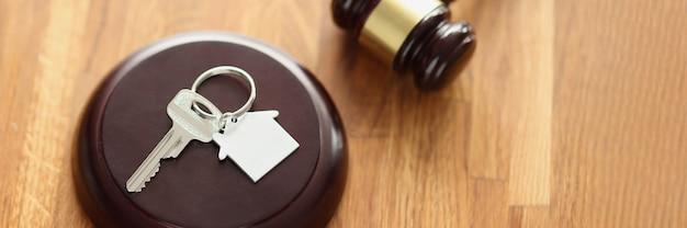 Jueces martillo de madera y llaves de la casa sobre la mesa. venta de bienes raíces en concepto de subasta
