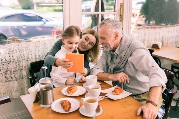 Juega con chica. pareja de abuelos sosteniendo tableta naranja mientras juega con su niña sentada en la panadería