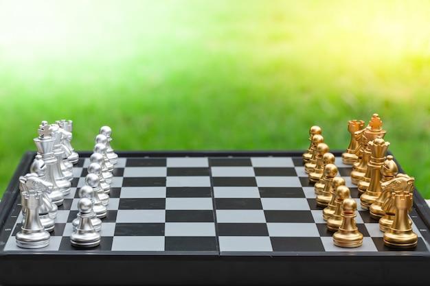 Juego de ajedrez, coloca el tablero esperando jugar en piezas de oro y plata sobre hierba verde