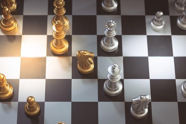 Juego de ajedrez, establece el tablero esperando jugar en piezas de oro y plata borrosas