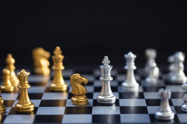 Juego de ajedrez, establece el tablero esperando jugar en piezas de oro y plata desenfocado