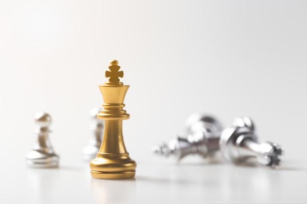 Juego de ajedrez oro rey permanente y fondo plateado, concepto de estrategia empresarial.