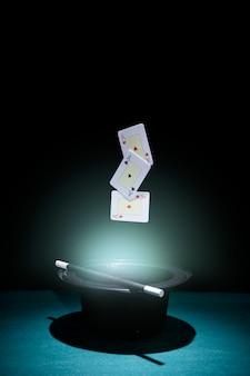 Juego de ases jugando a las cartas en el aire sobre el sombrero de copa negro iluminado