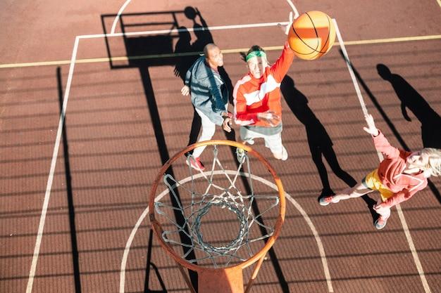 Juego de básquetbol. vista superior del agradable equipo joven jugando al baloncesto juntos