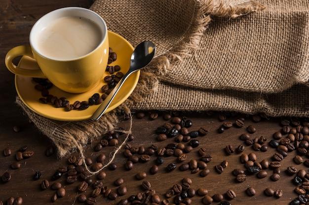 Juego de café en cilicio cerca de granos de café