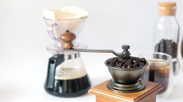 Juego de café, granos de café tostados frescos en el molino, molinillo de café manual y botella de vidrio, goteo de papel de café negro aislado