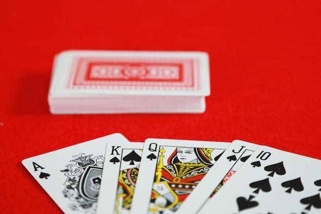 Juego de cartas de póker royal straight flush en mano en el juego de naipes en casino
