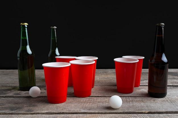 Juego de cerveza pong en mesa de madera.