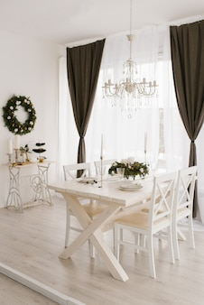 Juego de comedor mesa de madera blanca con sillas en un luminoso salón decorado para navidad y año nuevo en un estilo clásico