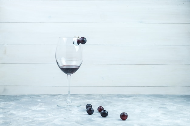 Juego de una copa de vino y uvas negras sobre fondo gris y madera sucio. vista lateral.