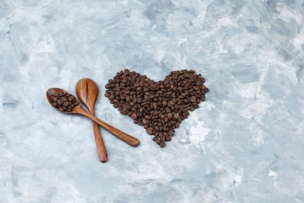 Juego de cucharas de madera y granos de café sobre un fondo de yeso gris. endecha plana.